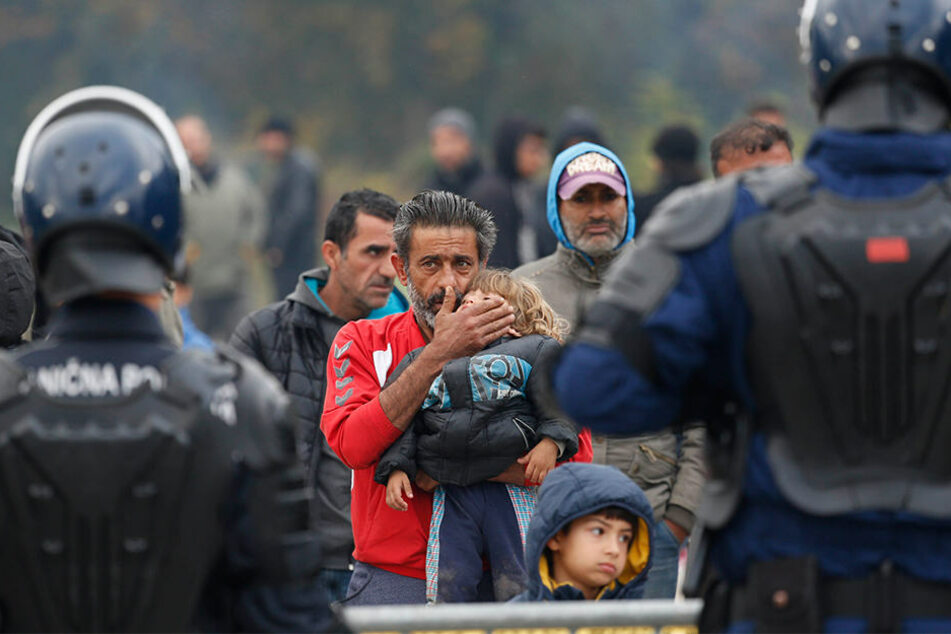Ein Migrant hält ein Kind vor einer Polizeiabsperrung am Grenzübergang von Maljevac zwischen Bosnien-Herzegowina und Kroatien.