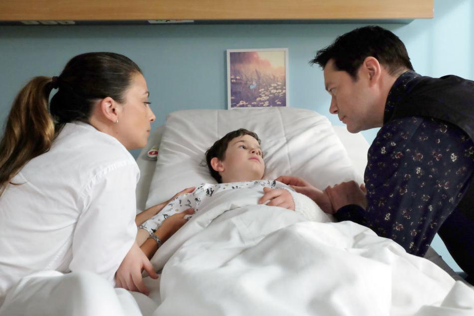 Der Sohn von Oberarzt Dr. Philipp Brentano (r.) wird in die Klinik eingeliefert. Plötzlich ist Oskar (M.) bewusstlos, blutet stark. Was hat er nur?