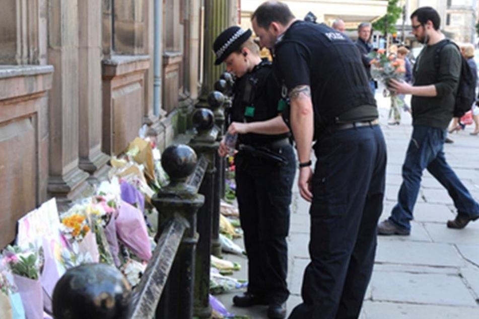 Britische Polizisten vor Blumensträußen und Beileidsbekundungen, die für die Opfer niedergelegt wurden.