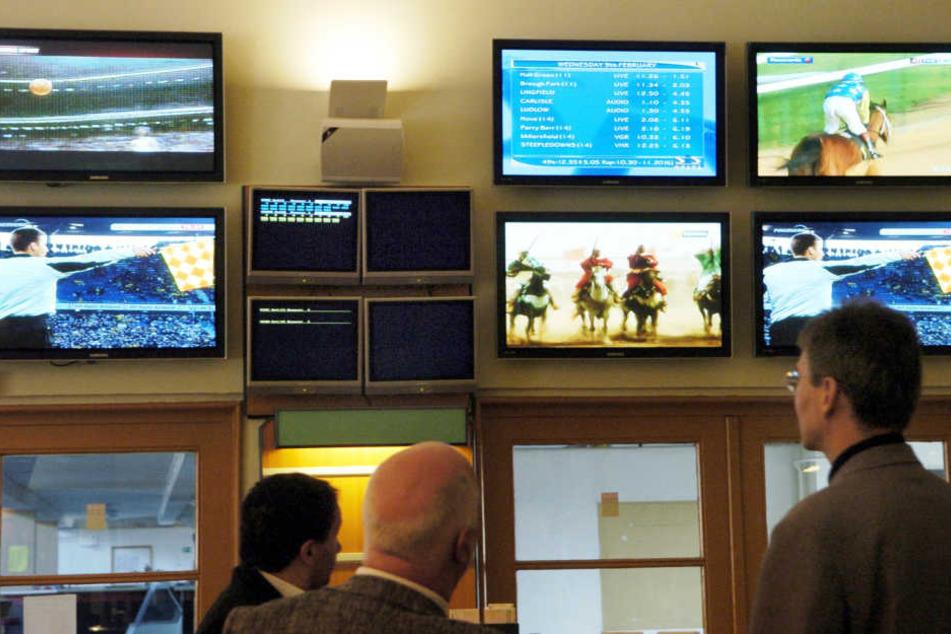 In einem Wettlokal verfolgen Besucher Sportwettkämpfe auf den Monitoren (Symbolbild)