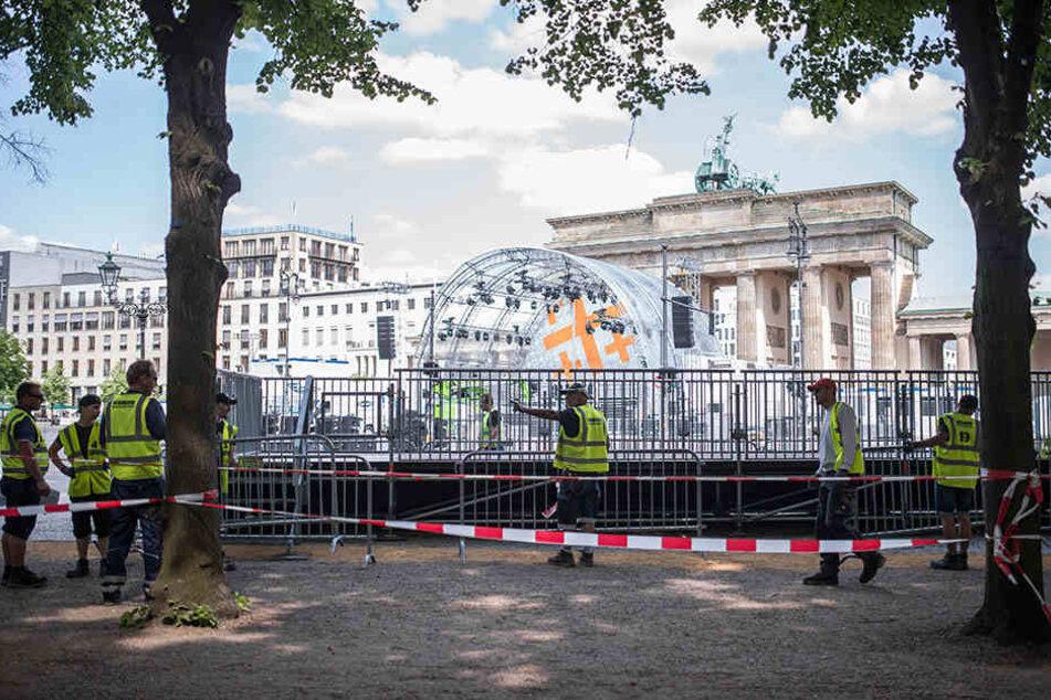 Bauarbeiter stellen vor dem Brandenburger Tor in Berlin Straßenabsperrungen in Vorbereitung auf den Evangelischen Kirchentag auf.