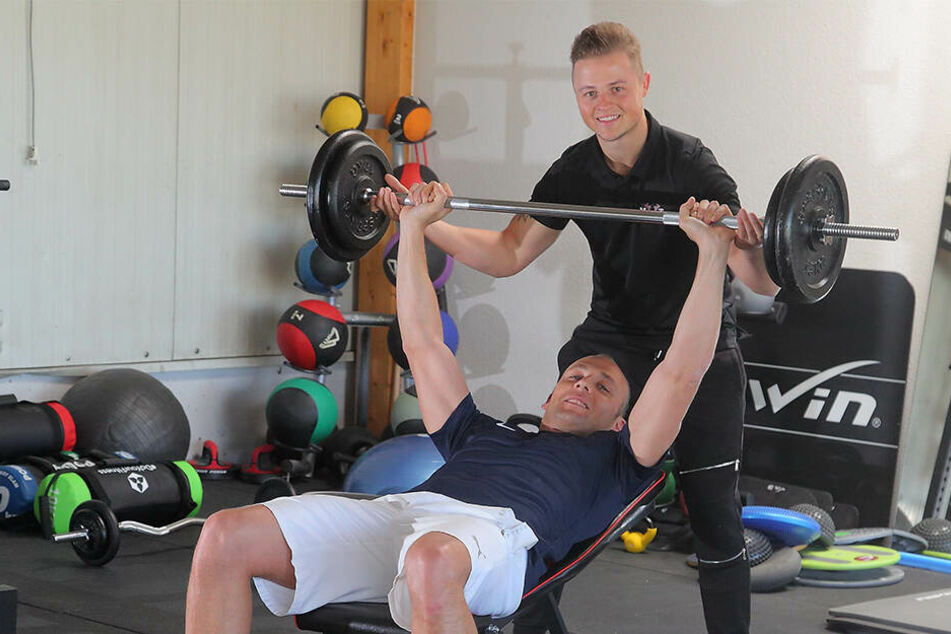 Geschäftsführer Tobias Schwald (34, v.) stemmt unter Aufsicht seines Bruders Michael (27) Gewichte.