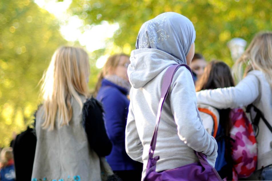 Ein Kind mit Kopftuch steht am Rand einer Schülergruppe. (Symbolbild)