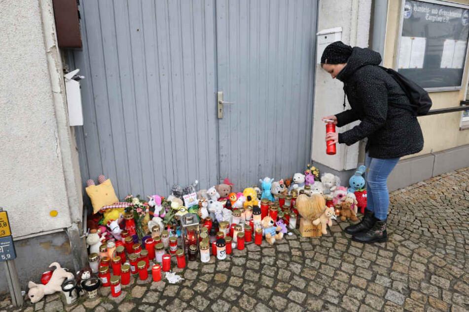 Eine Frau stellt vor dem Haus in Torgelow eine Kerze auf, wo am 12.01.2019 ein sechsjähriges Mädchen ums Leben kam.