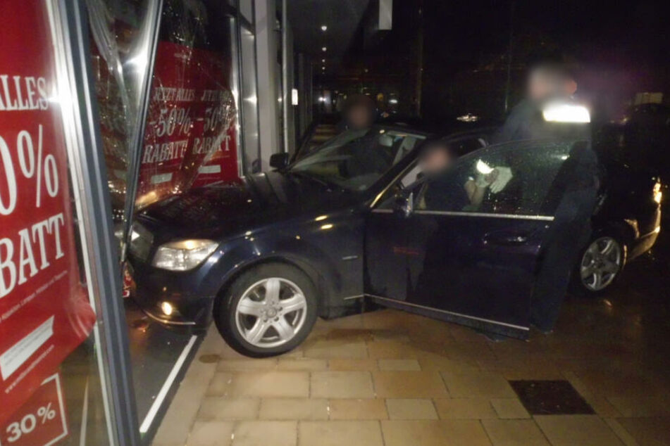 Das Auto krachte in das Schaufenster, die Polizeibeamten versuchten den Mann aus seinem Fahrzeug zu holen.