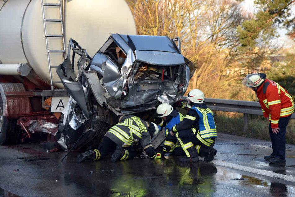 Rettungskräfte arbeiten an einem Wagen der noch unter dem Sattelzug klemmt