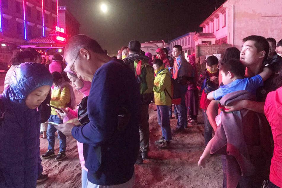 Touristen stehen mit bangen Blicken auf einer Straße. Auch sie sind von dem Erdbeben betroffen.