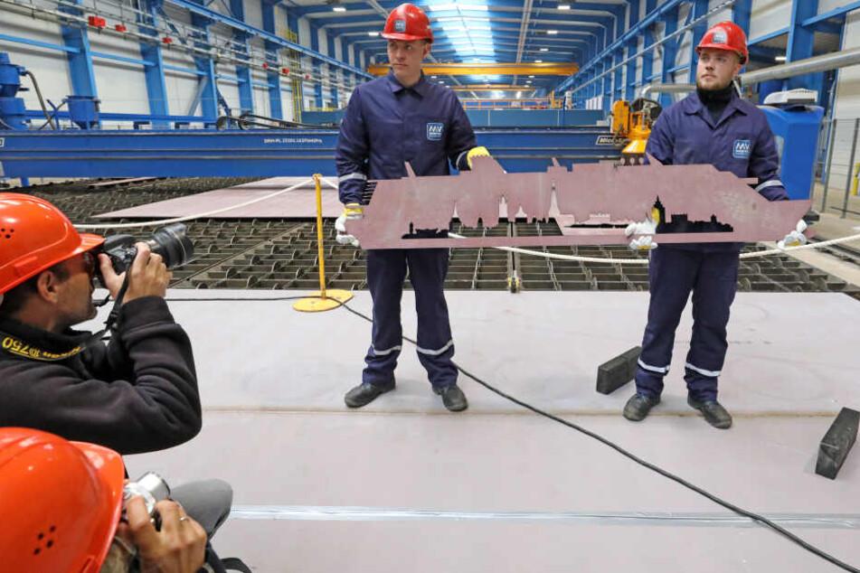 Beim offiziellen Brennbeginn für das zweite Kreuzfahrtschiff der Global-Class präsentieren die Auszubildenden Erik Ruwoldt (links) und Richard Knop die ausgeschnittene Silhouette des Kreuzfahrtschiffes in einer Stahlplatte.