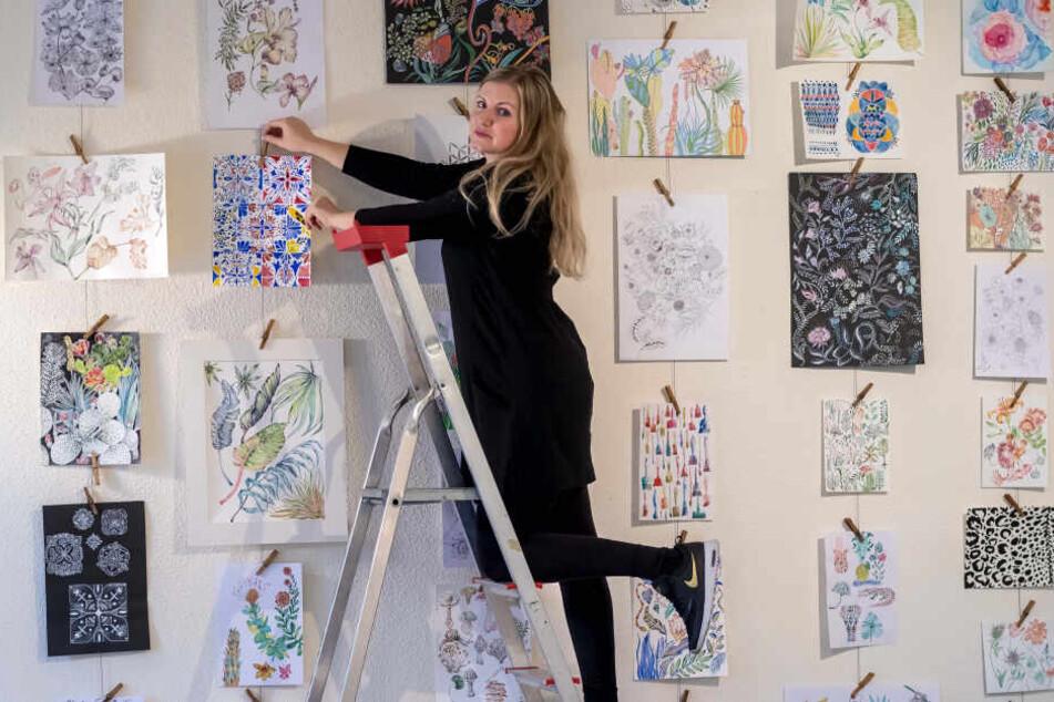"""Die Designerin Carolin Tennstaedt (32) hängt ihre Entwürfe im Kulturzentrum """"Erzhammer"""" auf. Manche Designs stammen noch aus ihrer Studienzeit."""