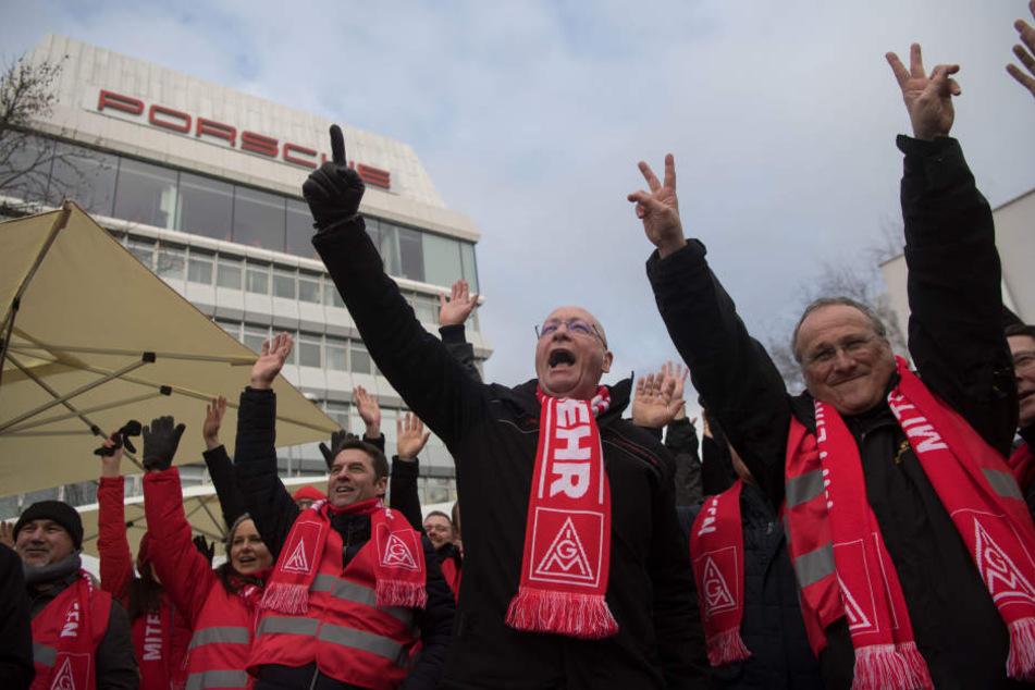 Uwe Hück, Betriebsratsvorsitzender der Porsche AG (2.vr), hält während eines Warnstreiks vor dem Porsche-Stammwerk mit Streikenden die Arme nach oben. (Archivbild)