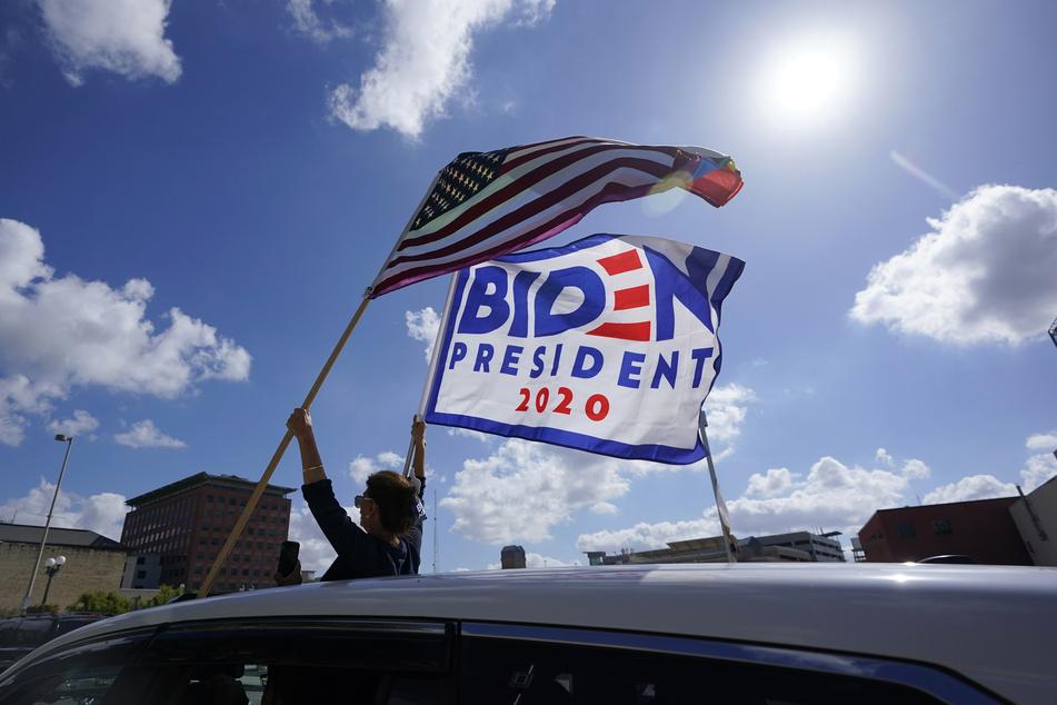 San Antonio: Unterstützer des designierten Präsidenten J. Biden und der designierten Vizepräsidentin K. Harris halten feierlich Fahnen mit Bidens Namen aus einem Auto.