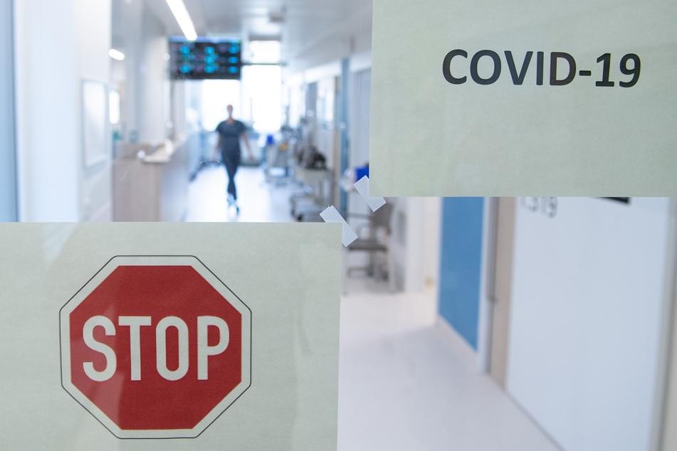 Eine Frau geht auf der Corona-Intensivstation im Universitätsklinikum Carl Gustav Carus Dresden hinter einer Glastür einen Gang entlang.