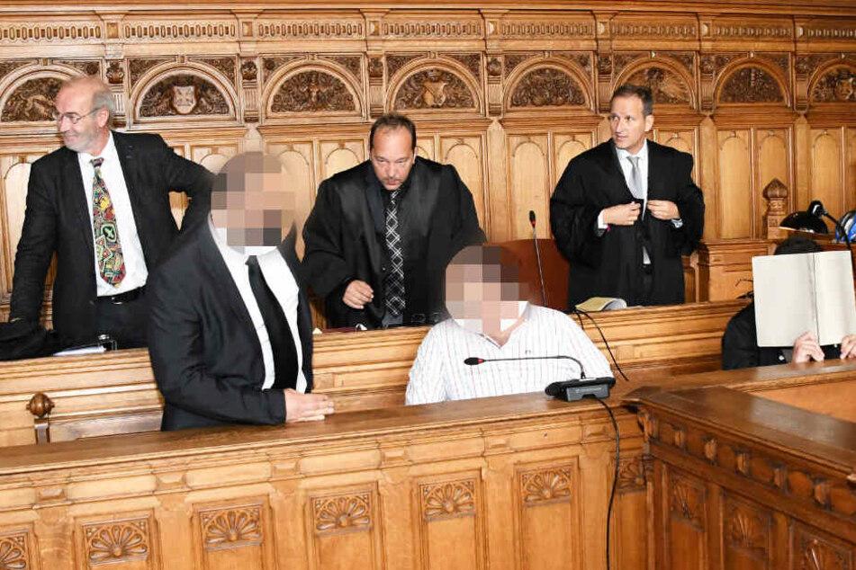 Die drei Angeklagten sitzen bei Prozessbeginn im Landgericht Bremen. (Archivbild)