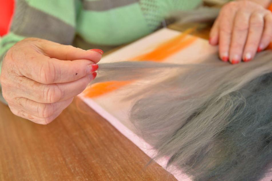 Die gekämmte Wolle wird nicht auf die Leinwand geklebt, sondern gelegt.