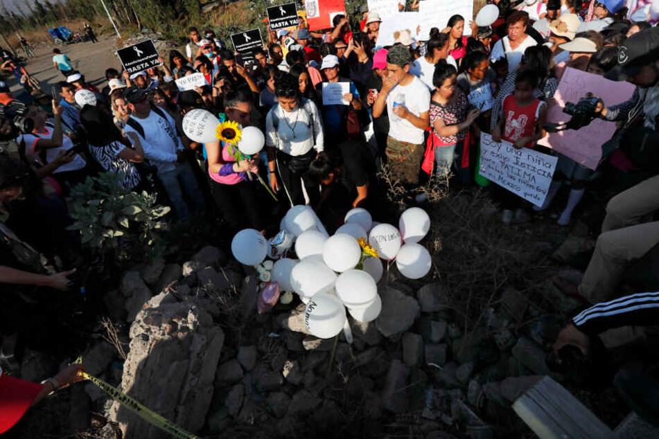 Demonstranten errichten an der Stelle, an der die Leiche eines siebenjährigen Mädchens, das ermordet wurde, gefunden wurde, ein Denkmal mit Blumen, Luftballons und Kerzen.