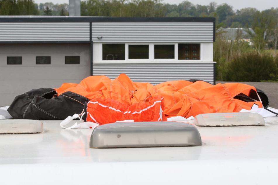 Der Fallschirm eines der Verunglückten liegt auf dem Dach eines Wohnmobils auf dem Parkplatz am Flugplatz.