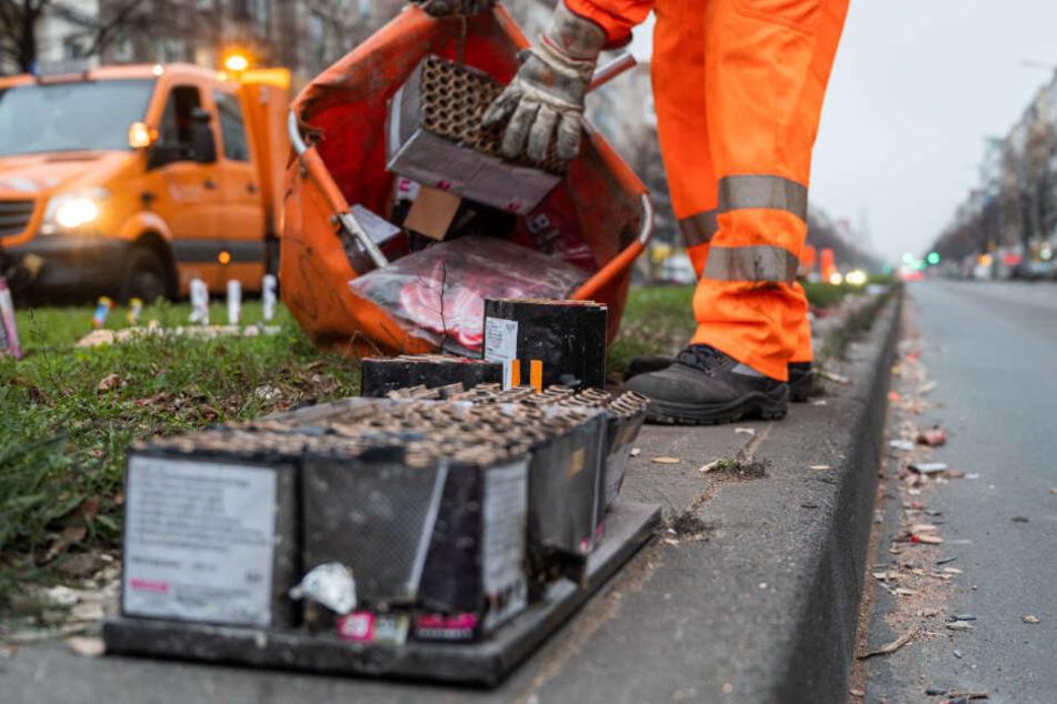 Ein Mitarbeiter der Berliner Stadtreinigung BSR sammelt abgebranntes Feuerwerk von der Straße auf.