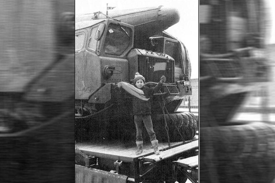 Ein Kind vor einem beladenen Raketentransporter.