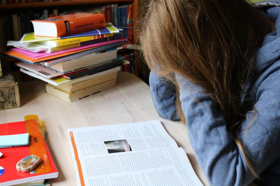 Ein Kind sitzt am Schreibtisch und vergräbt beim Lernen das Gesicht in den Händen. (Symbolbild)