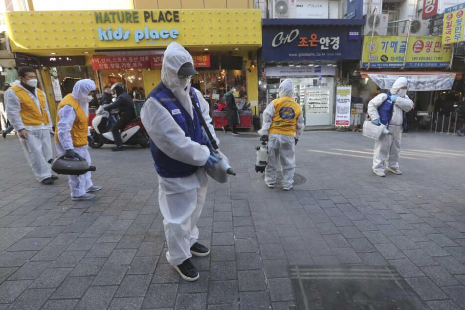 Arbeiter in Schutzkleidung versprühen Desinfektionsmittel auf eine Straße. Adidas reagiert mit der Maßnahme auf die Empfehlung der Behörden.
