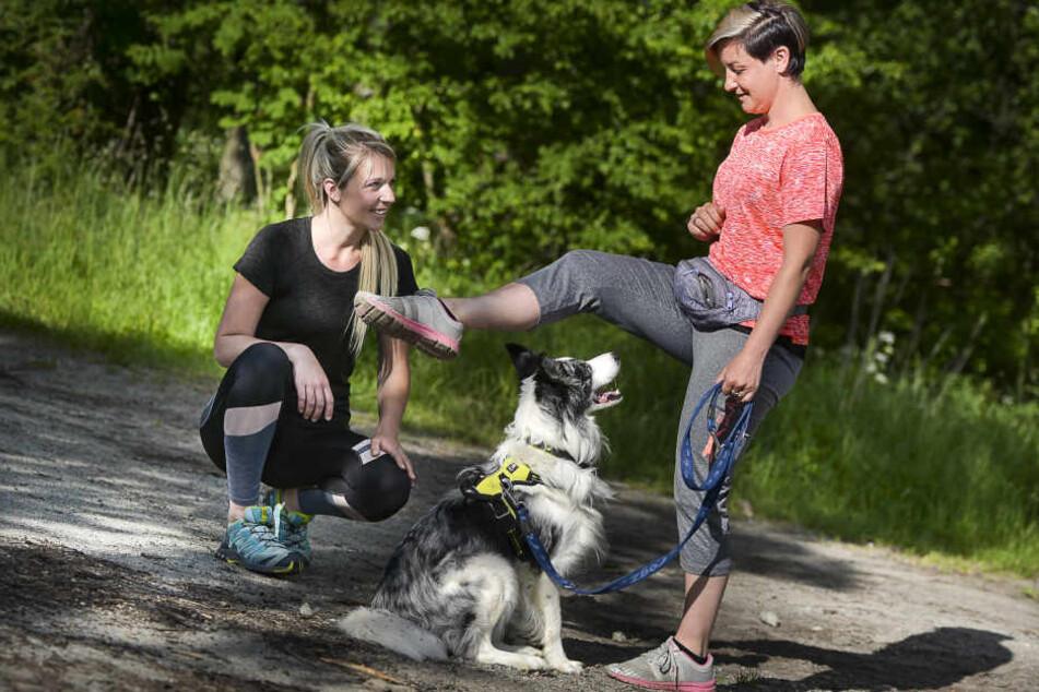 """Hoch und rüber das Bein! Hund """"Sky"""" muss sitzenbleiben, damit  Kursteilnehmerin Stephanie Neumann unter Lisas Anleitung die Fitness-Übung  machen kann."""