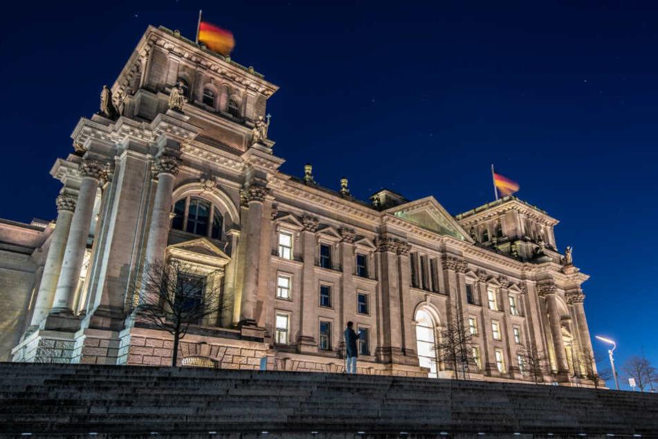 Ein Mann steht am Abend vor dem Reichstag. (Symbolbild)