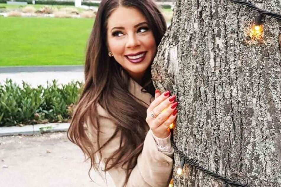 Jenny versteckt sich hinter einem Baum.