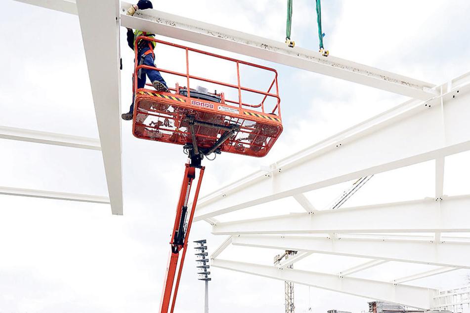 Arbeiten in der Höhe. Auf einer Hebebühne steht der Arbeiter und schraubt die Stahlbalken zusammen.