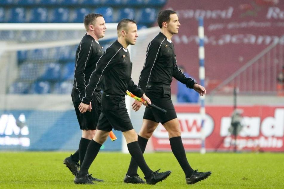 Schiedsrichter Benjamin Brand und seine Assistenten gehen vom Feld.
