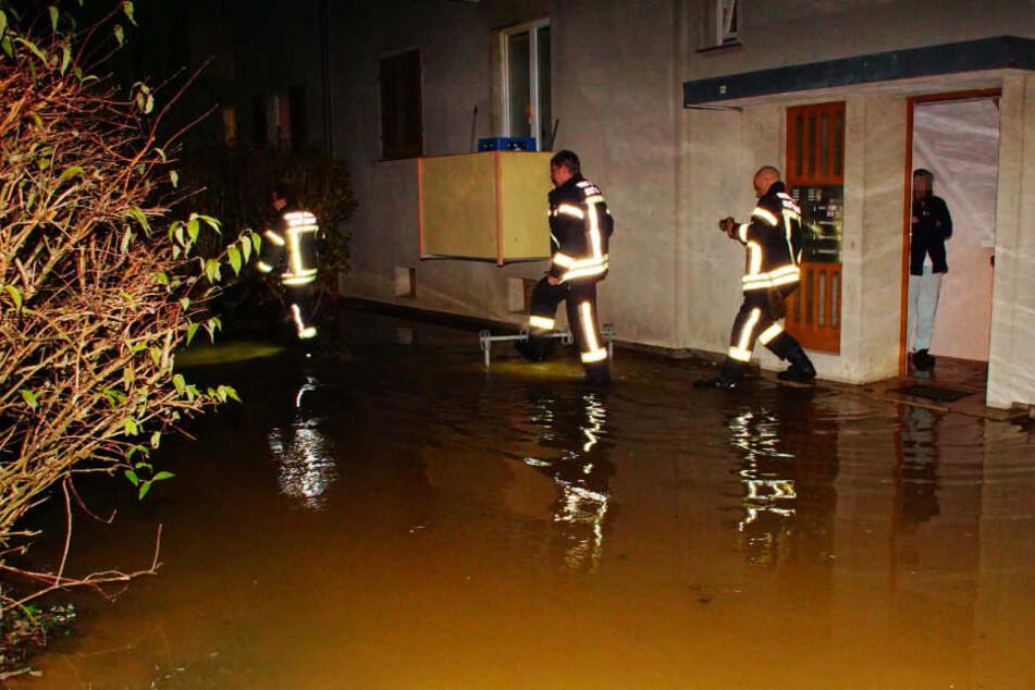 Feuerwehrleute laufen durch die Überschwemmung vor dem Mehrfamilienhaus.