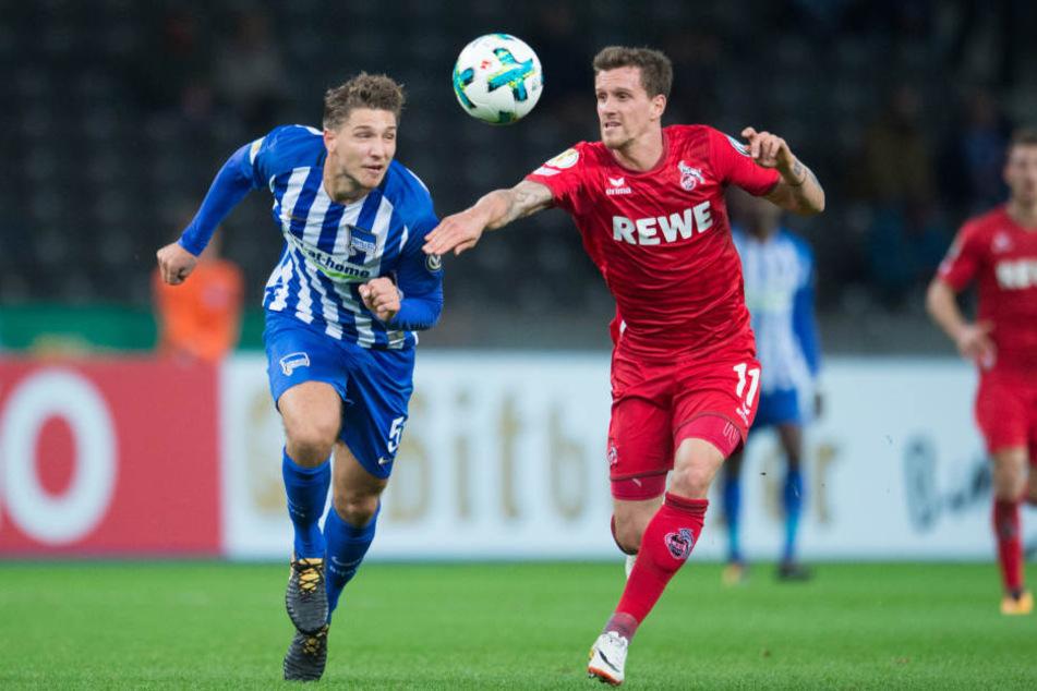 Berlins Niklas Stark (l) und Kölns Simon Zoller laufen zusammen zum Ball.