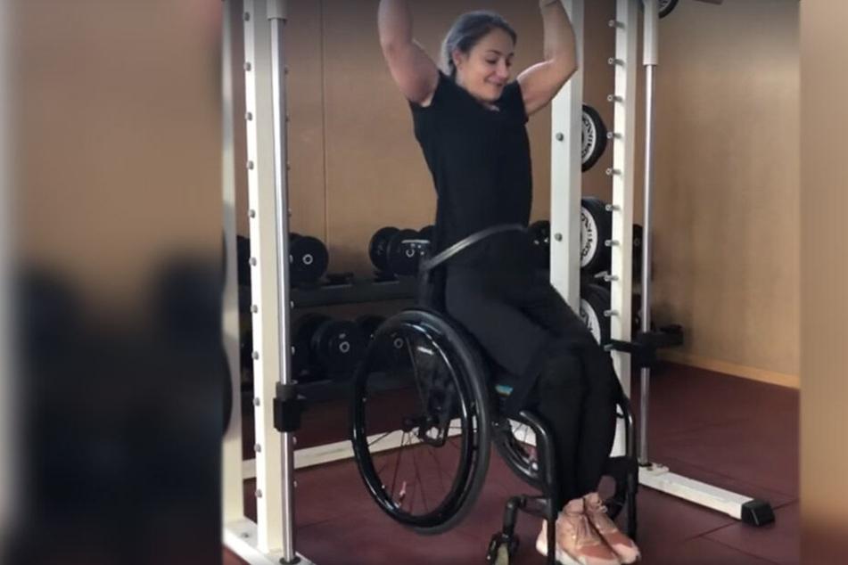 Die 29-Jährige macht einen Klimmzug mit dem Rollstuhl.
