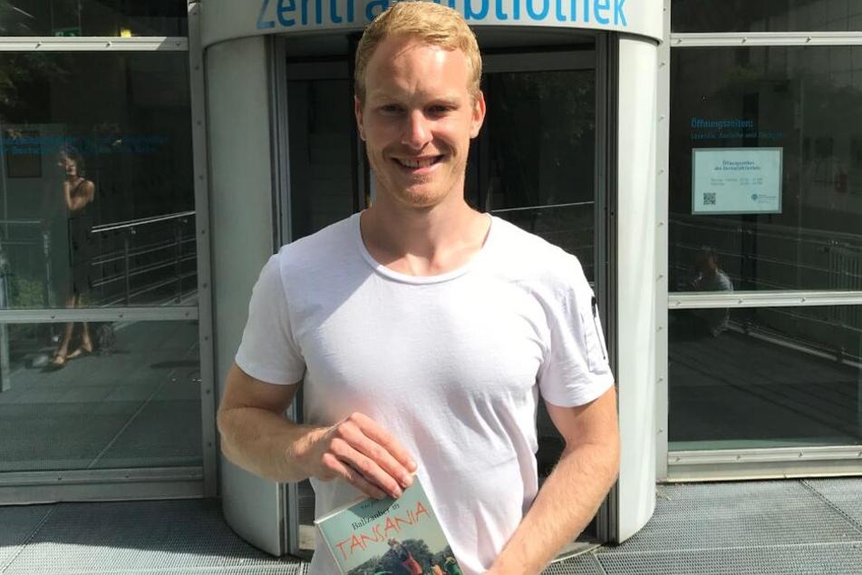 Der Sportstudent Tim Jost (25) mit seinem Buch vor der Kölner Sporthochschule.