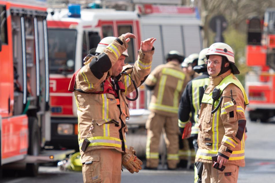 Feuerwehrleute stehen auf der Straße vor dem Haus und bereiten Nachlöscharbeiten vor (Symbolbild).