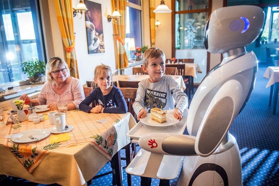 """""""Amy"""" serviert Hannelore Kossack (64) und ihren Enkeln Mia und Max (beide 6) ein Stück Kuchen."""