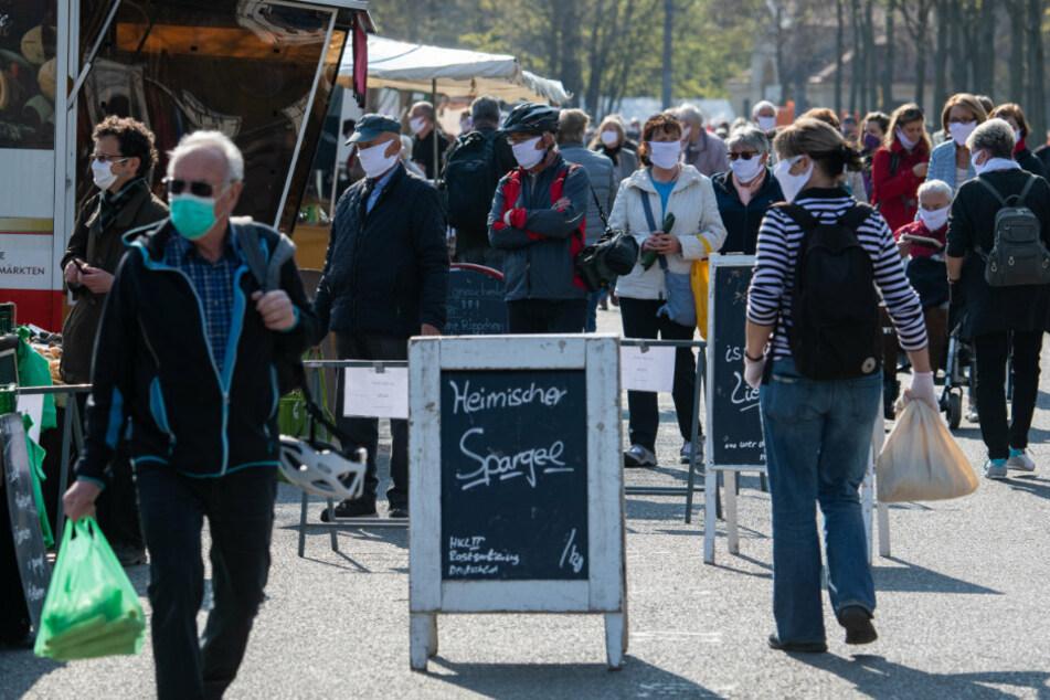 Besucher auf dem Wochenmarkt in Dresden tragen Mundschutz.
