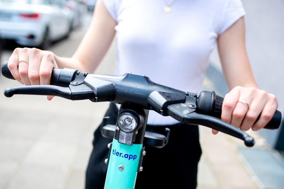 Eine junge Frau steht auf einem E-Scooter des Elektro-Tretroller-Sharing-Anbieters Tier Mobility. Seit einem Jahr können E-Scooter in Deutschland genutzt werden.