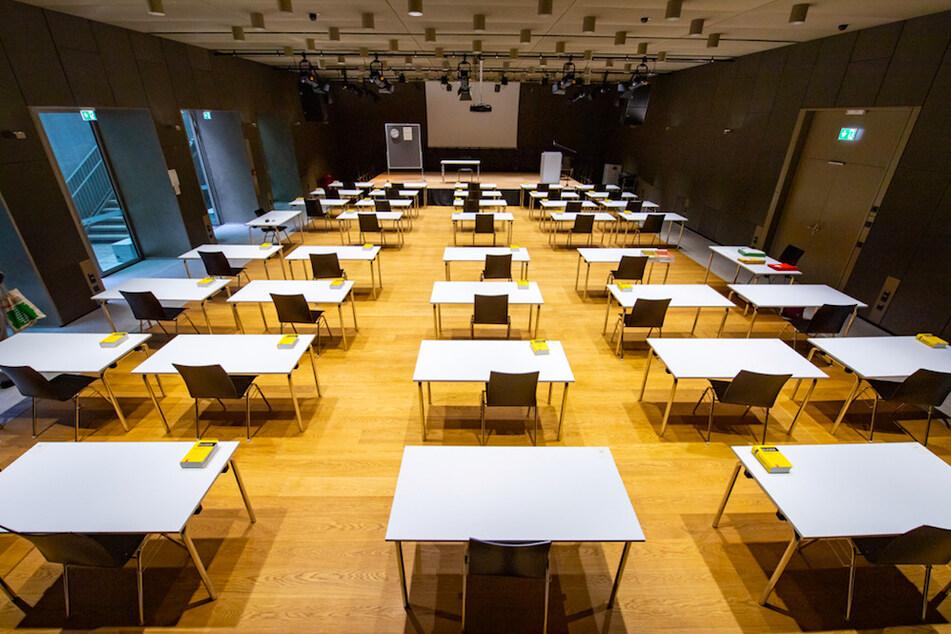 Mit weiten Abstand stehen die Tische zur Abiturprüfung Deutsch in einer Schulaula.