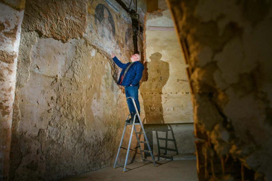 Piotr Koper steht im Ballsaal des Palac Struga (Schloss Adelsbach) auf einer Leiter und zeigt auf freigelegte jahrhundertealte Gemälde.