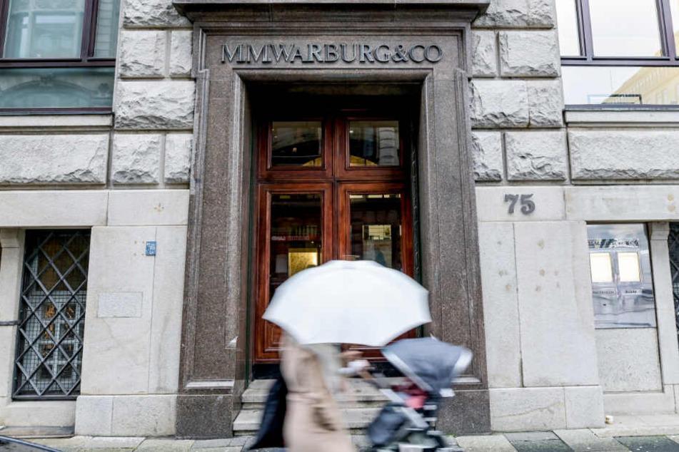 Passanten gehen an der Eingangstür des Bankhauses M.M.Warburg & CO in Hamburg vorbei.