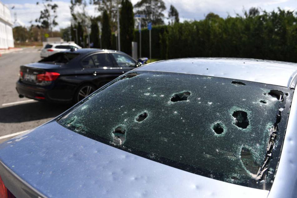 Von Hagel beschädigte Autos stehen vor dem alten Parlamentsgebäude in Canberra geparkt.