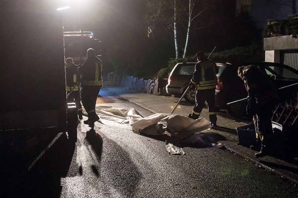 Mitarbeiter der Feuerwehr beseitigen Spuren am Tatort.