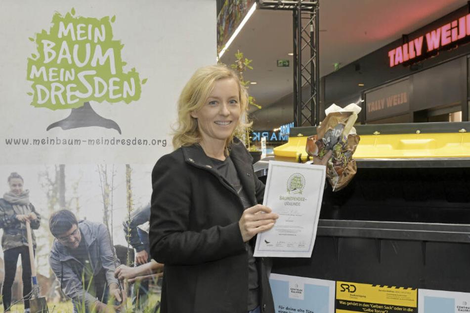 Anne Richter (43) gibt eine Plastiktüte ab, dafür wird nun ein Baum gepflanzt.