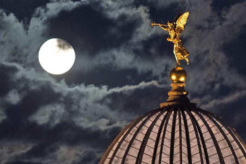 Der aufgehende Mond ist am 05.09.2017 neben der vergoldeten Figur des Posaunenengels Fama auf dem Dach der Kunstakademie in Dresden zu sehen.
