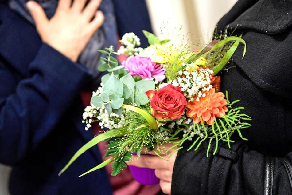 Angehörige warten mit Blumen in den Händen auf den Prozessbeginn.