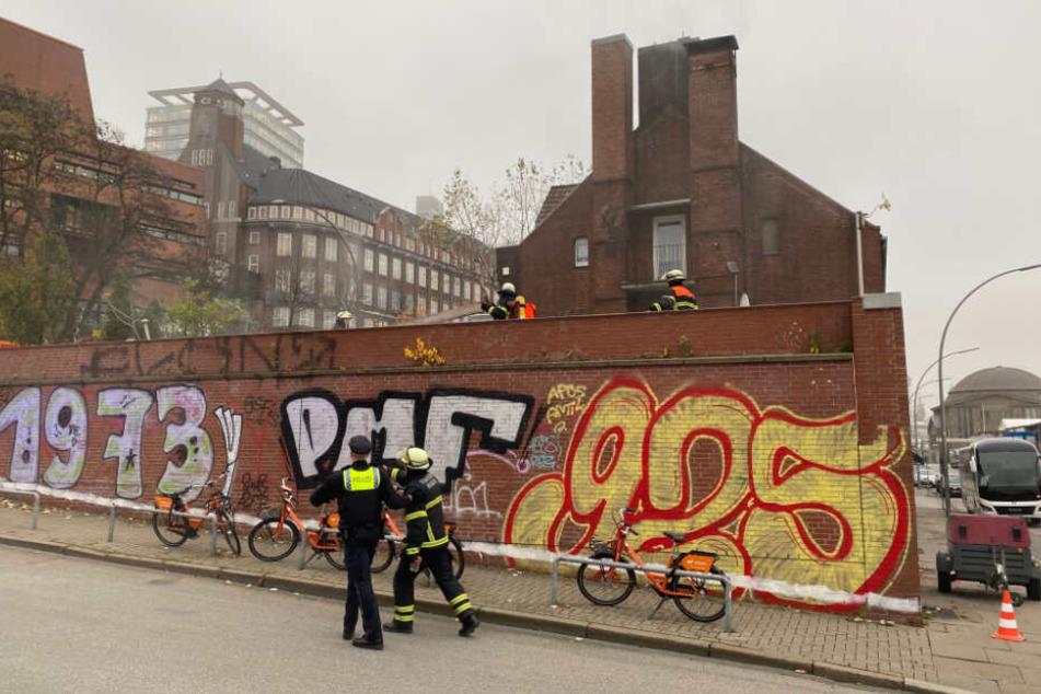 Feuerwehrleute untersuchen die Baustelle, aus der Rauch aufsteigt.
