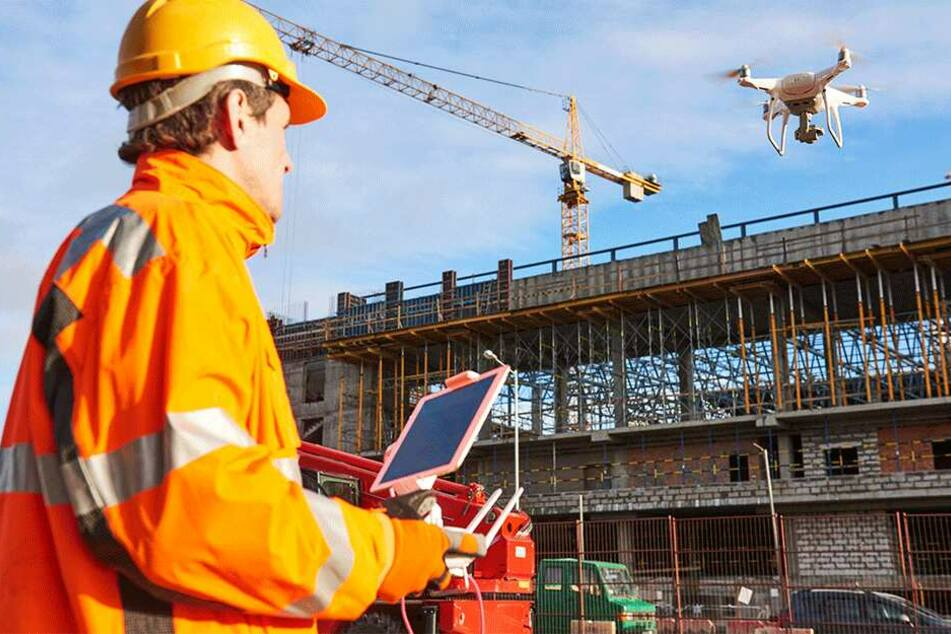Ein Ingenieur nutzt eine Drohne als fliegendes Auge bei der Inspektion einer Baustelle. Die Technik kommt in der Wirtschaft immer häufiger zum Einsatz.