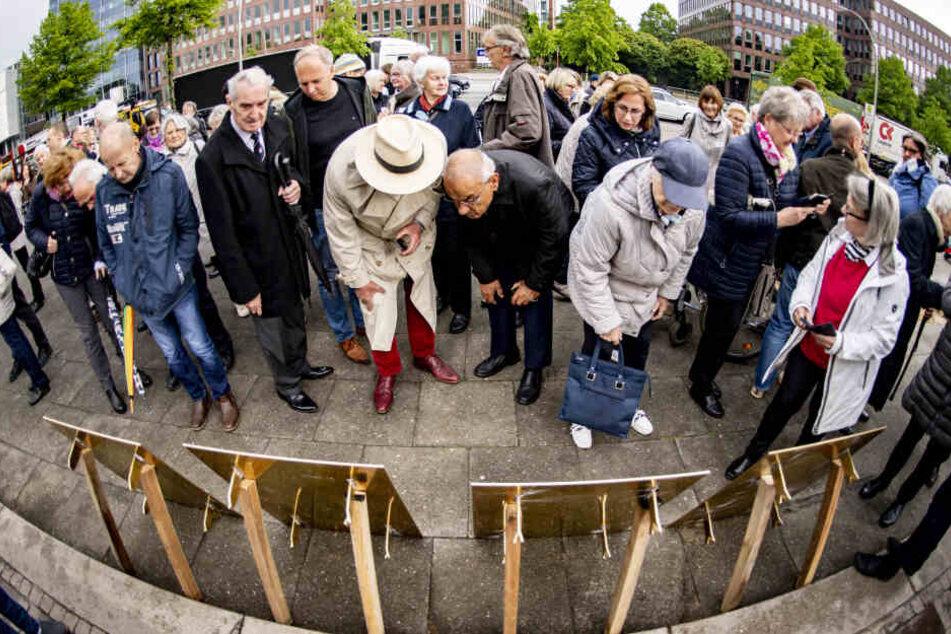Menschen betrachten die vor der Verlegung von vier aufgestellten neuen Michel-Tafel.