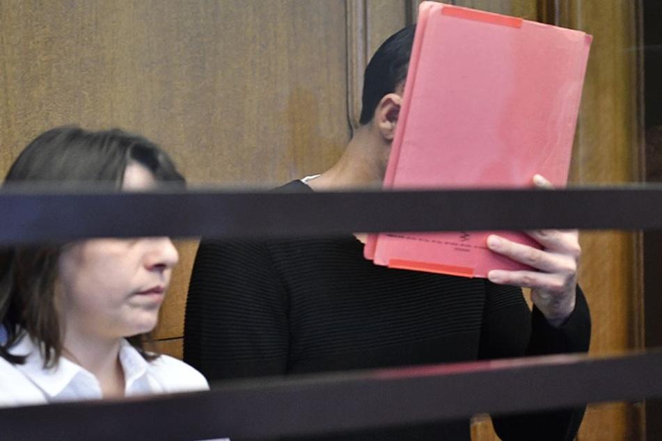 Der Angeklagte Svetoslav S. verbirgt sein Gesicht hinter einer Mappe.