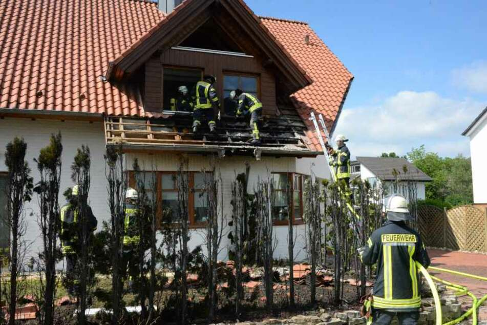 Hinter der völlig verkohlten Hecke löschen Feuerwehrleute Glutnester im Bereich des Daches.